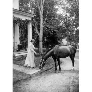 Helen Keller, full length portrait standing on lawn holding reins to a